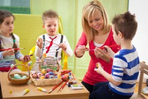 kids painting easter eggs with teacher