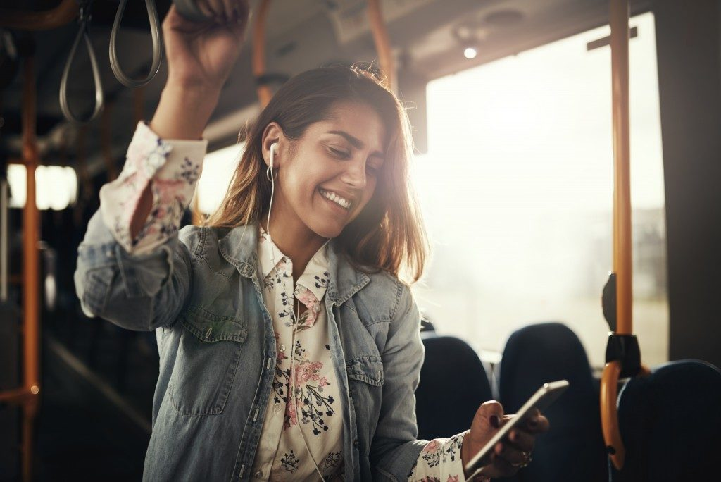 Woman listening to music in her phone while inside the bus