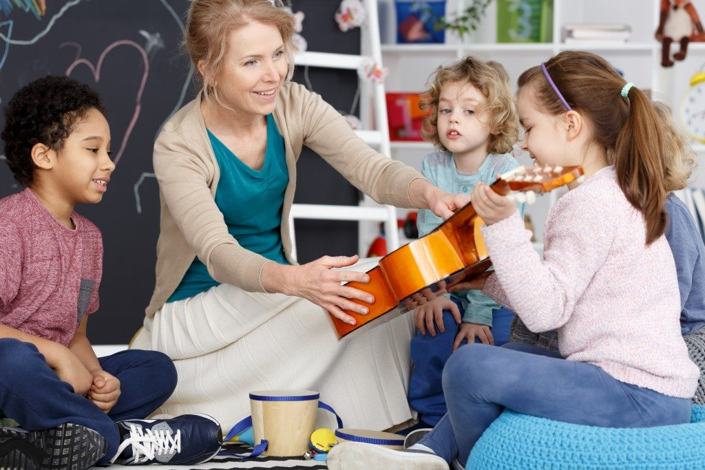 Teacher teaching her students how to play the guitar