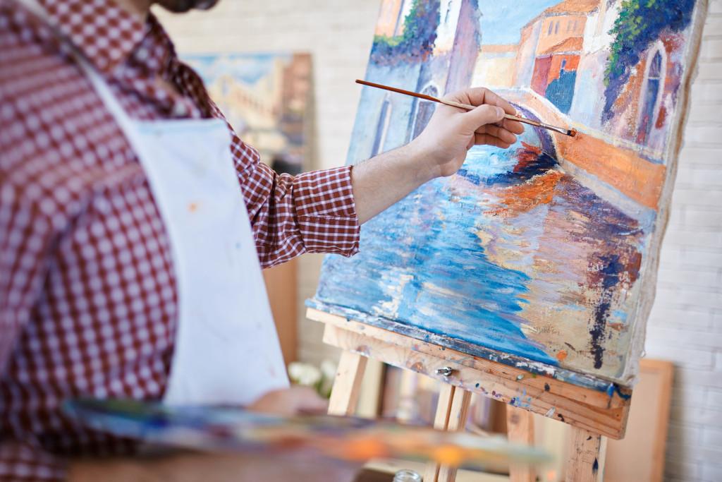 man painting a scene